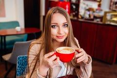 Mujer joven hermosa con una taza de café roja en un café Mujer que bebe el café caliente del latte en la cafetería acogedora Imagen de archivo