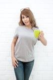 Mujer joven hermosa con una taza de situación del café Foto de archivo