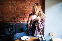 Mujer joven hermosa con una taza de té en una tienda del café Imagenes de archivo