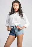 Mujer joven hermosa confiada en los pantalones cortos blancos de la camisa y del dril de algodón Fotografía de archivo