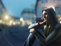 Mujer joven hermosa contra una ciudad por noche imagen de archivo libre de regalías