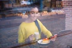 Mujer joven hermosa de la raza mixta vista a través de la ventana de la panadería Fotografía de archivo libre de regalías