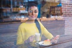Mujer joven hermosa de la raza mixta vista a través de la ventana de la panadería Fotos de archivo
