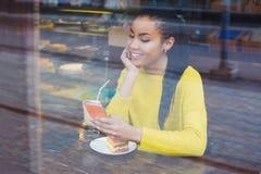 Mujer joven hermosa de la raza mixta vista a través de la ventana de la panadería Imagen de archivo