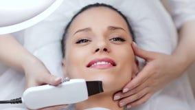 Mujer joven hermosa de la visión superior que disfruta de procedimiento de limpiamiento de peladura ultrasónico en el salón de be metrajes