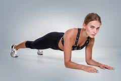 Mujer joven hermosa del ajuste deportivo en sujetador de la ropa de deportes y cacerola negra Foto de archivo libre de regalías