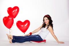 Mujer joven hermosa del día de tarjeta del día de San Valentín que lleva el vestido rojo y que sostiene los globos rojos Fotos de archivo