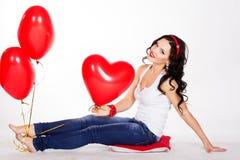 Mujer joven hermosa del día de tarjeta del día de San Valentín que lleva el vestido rojo y que sostiene los globos rojos Imagen de archivo libre de regalías