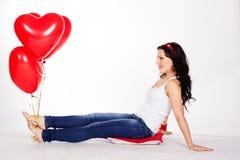 Mujer joven hermosa del día de tarjeta del día de San Valentín que lleva el vestido rojo y que sostiene los globos rojos Fotos de archivo libres de regalías