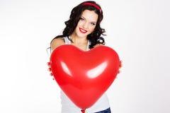 Mujer joven hermosa del día de tarjeta del día de San Valentín que lleva el vestido rojo y que sostiene los globos rojos Imagen de archivo