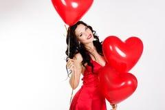 Mujer joven hermosa del día de tarjeta del día de San Valentín que lleva el vestido rojo y que sostiene los globos rojos Imagenes de archivo