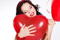 Mujer joven hermosa del día de tarjeta del día de San Valentín que lleva el vestido rojo y que sostiene los globos rojos Imágenes de archivo libres de regalías