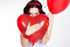 Mujer joven hermosa del día de tarjeta del día de San Valentín que lleva el vestido rojo y que sostiene los globos rojos Fotografía de archivo