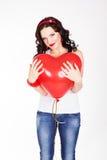 Mujer joven hermosa del día de tarjeta del día de San Valentín que lleva el vestido rojo y que sostiene los globos rojos Fotografía de archivo libre de regalías
