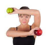 Mujer joven hermosa del deporte con la manzana roja y verde, aislada en blanco Imágenes de archivo libres de regalías