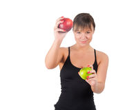 Mujer joven hermosa del deporte con la manzana roja y verde, aislada en blanco Imagen de archivo