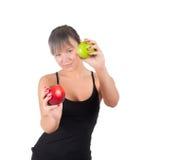 Mujer joven hermosa del deporte con la manzana roja y verde, aislada en blanco Fotografía de archivo libre de regalías