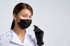 Mujer joven hermosa del doctor en máscara médica protectora y ojos sonrientes de los guantes negros médicos Fondo del retrato del foto de archivo
