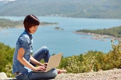 Mujer joven hermosa del freelancer que usa el ordenador portátil Imagenes de archivo