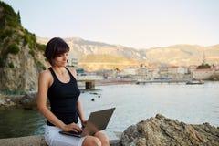 Mujer joven hermosa del freelancer que usa el ordenador portátil Imagen de archivo libre de regalías