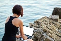 Mujer joven hermosa del freelancer que usa el ordenador portátil Fotos de archivo libres de regalías