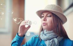 Mujer joven hermosa del inconformista en burbujas que soplan del sombrero Imagen de archivo libre de regalías