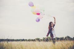 Mujer joven hermosa del inconformista que se sostiene con colorido de globos fotos de archivo