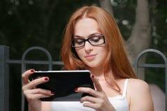 Mujer joven hermosa del pelirrojo con una tableta-PC en el parque que se inclina usando la pantalla táctil imagen de archivo libre de regalías