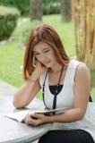 Mujer joven hermosa del pelirrojo que escribe un cuaderno Fotos de archivo