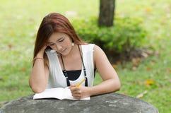 Mujer joven hermosa del pelirrojo que escribe un cuaderno Foto de archivo libre de regalías