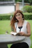 Mujer joven hermosa del pelirrojo que lee al aire libre Fotografía de archivo libre de regalías