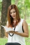 Mujer joven hermosa del pelirrojo que lee un libro Imagen de archivo libre de regalías