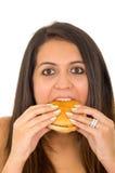 Mujer joven hermosa del retrato que presenta para la cámara que come la hamburguesa mientras que hace la expresión facial culpabl Imágenes de archivo libres de regalías