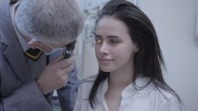 Mujer joven hermosa del retrato que se sienta en la silla del oculista del doctor que hace al oftalmólogo profesional de la prueb metrajes