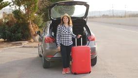 Mujer joven hermosa del viajero con la maleta cerca del tronco de coche almacen de metraje de vídeo