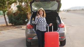 Mujer joven hermosa del viajero con la maleta cerca del tronco de coche metrajes