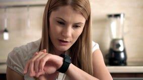 Mujer joven hermosa dentro que se sienta en una cocina que envía un mensaje de la voz vía su reloj elegante almacen de video