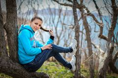 Mujer joven hermosa deportiva que se sienta en la tierra con la hierba y las flores de la primavera que llevan la camiseta azul b Imagen de archivo