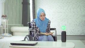 Mujer joven hermosa discapacitada en hijab, silla de ruedas, voz de las aplicaciones como ayudante para el estudio y la educación