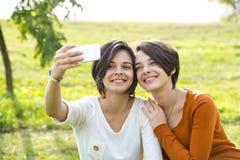 Mujer joven hermosa dos que toma su foto con Smartphone Foto de archivo libre de regalías