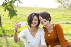Mujer joven hermosa dos que toma su foto con Smartphone Fotografía de archivo