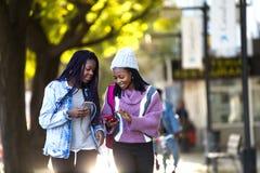 Mujer joven hermosa dos que usa el teléfono móvil en la calle Fotos de archivo libres de regalías