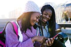 Mujer joven hermosa dos que usa el teléfono móvil en la calle Foto de archivo libre de regalías