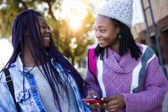 Mujer joven hermosa dos que usa el teléfono móvil en la calle Imagen de archivo libre de regalías
