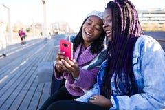 Mujer joven hermosa dos que usa el teléfono móvil en la calle Fotografía de archivo libre de regalías