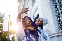 Mujer joven hermosa dos que usa el teléfono móvil en la calle Imagenes de archivo
