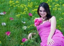 Mujer joven hermosa en alineada rosada en campo verde Fotos de archivo libres de regalías