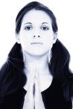 Mujer joven hermosa en azul con las manos de la meditación o del rezo Foto de archivo libre de regalías