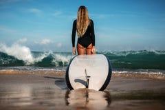 Mujer joven hermosa en bikini con el tablero de resaca en la playa de la isla tropical Fotos de archivo libres de regalías