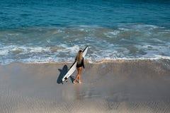 Mujer joven hermosa en bikini con el tablero de resaca en la playa de la isla tropical Fotos de archivo
